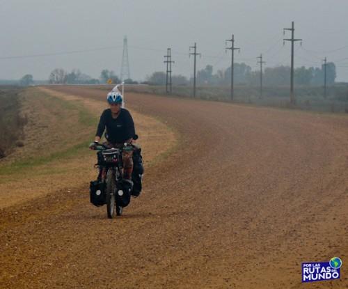 Viajar en bici por una ruta de ripio y con niebla